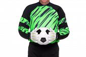 Photo of a football or soccer goalkeeper wearing gloves and holding a ball, isolated on a white back