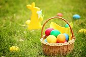 Colorful eggs in wicker basket on green grass. Easter hunt concept poster