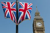 Two Union Flags flying in front of the clock tower, commonly referred to as Big Ben, of the Palace o
