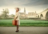 Beautiful young woman holding a suitcase with village in the background poster