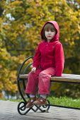 Kid Sitting On The Bench Outdoors poster