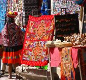 Peruvian Indian Woman Looking At Colorful Textiles