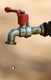 pic of water shortage  - Image shows a tap dripping water against a dry background - JPG