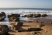 Waves Breaking On Rocky Beach On Durban Coastline With Footprints In Sand poster