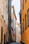 Stockholm Narrow Street. Orange, Yellow Houses And Street Lights. View From Below Of A Cozy Narrow M poster