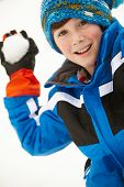 stock photo of snowball-fight  - Young Boy About To Throw Snowball Wearing Woolly Hat - JPG