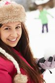 stock photo of snowball-fight  - Teenage Couple Having Snowball Fight Wearing Fur Hats - JPG