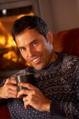 Middle Aged Man Relaxing With Hot Drink By Cosy Log Fire