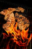image of flame-grilled  - barbecue meats on a fiery flaming grill - JPG