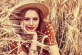 Romantic hippie girl sitting on a wheat field. Summer. Hippie, bohemian style. poster