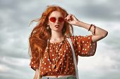 Portrait of a beautiful red-haired girl over sky background. Hair coloring. Hippie style. Bohemian s poster