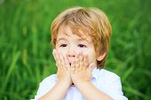 Funny Child Boy With Hands Close To Face Isolated On Green Background. Child Expressing Surprise Wit poster