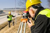 Land surveyors on highway measuring with theodolite