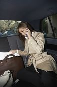 Hispanic businesswoman working in backseat of car