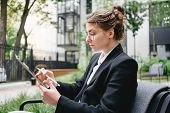 Portrait Young Businesswoman Sitting In Cafe On Veranda And With A Digital Tablet. Pensive Woman Wea poster
