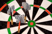 stock photo of fletching  - three darts missing the bullseye - JPG