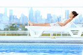 Urban luxury city lifestyle woman lying by pool relaxing in sun lounger during summer in Montreal, Q