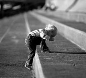 pic of stepping stones  - young child climbing stone steps with a lot of effort - JPG