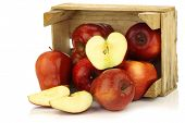Fresh and delicious red Ambrosia apples and a cut one in a wooden crate on a white background