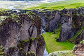 The Fyadrarglyufur Canyon, Iceland. River with glacial water flows between bizarre cliffs. Sheer cli poster