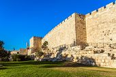 Adorable green lawn growing under ancient walls. Summer sunset. The fortress wall of old Jerusalem.  poster