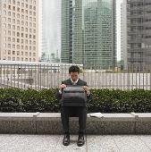 Businessman in urban scene looking in briefcase