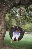 picture of tire swing  - Young girl sitting in tire swing - JPG