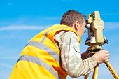 image of cartographer  - Surveyor engineer making measuring with optical equipment theodolite at blue sky background - JPG