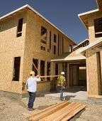 stock photo of friendship belt  - Two construction workers carrying lumber into unfinished building - JPG