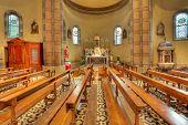 Bancas y altar entre columnas de la iglesia católica de Madonna Moretta en Alba, norte de Italia.