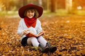 Cute Little Girl In Red Hat Sitting On Fall Leaves And Reading Interesting Book In Autumn Park poster