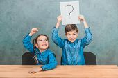 Schoolchildren Sitting At The Desk. Boy Is Raising Up The Sheet Of Paper With Exclamation Mark. Girl poster