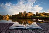 Beautiful Sunset Over Autumn Fall Lake With Crystal Clear Reflections In Pages Of Book Creative Conc