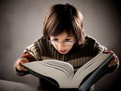 foto of geek  - Fine portrait of cute little boy reading book - JPG