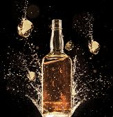 image of liquor bottle  - Concept of liquor splashing around bottle - JPG