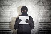 stock photo of shoplifting  - Arrested burglar concept thief with balaclava caught and arrested in front of the grunge concrete wall - JPG