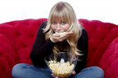 Young Blond Haired Girl Eat A Hand Of Popcorn On Red Sofa In Front Of White Background