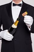 Waiter opening a bottle of champagne holding the cork in his other hand.