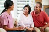 foto of visitation  - Nurse Making Notes During Home Visit With Senior Couple - JPG