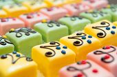 stock photo of petition  - many colorful petit fours with marzipan and chocolate - JPG