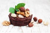 foto of mixed nut  - Basket with Mixed nuts on a old wooden background - JPG
