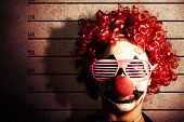 image of mug shot  - Grunge portrait of a funny clown criminal getting mug shot ID photo on police lines - JPG