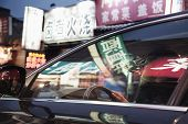 Young man driving through Beijing at night, illuminated store signs reflected off the windows of the