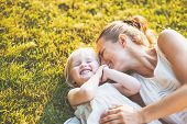 stock photo of stroll  - Happy mother and baby laying on meadow - JPG