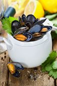 Mussels cooked with white wine sauce in a white pot