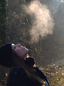 stock photo of exhale  - Beautiful girl breathing warm air during a cold autumn morning - JPG