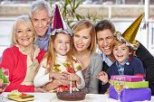 Happy family celebrating child's birthday party together with grandparents