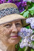 Mature Woman In A Garden With Lilac