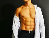 foto of nipple  - Muscular and tanned male torso isolated on black background