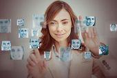 Businesswoman touching digital interface showing human faces